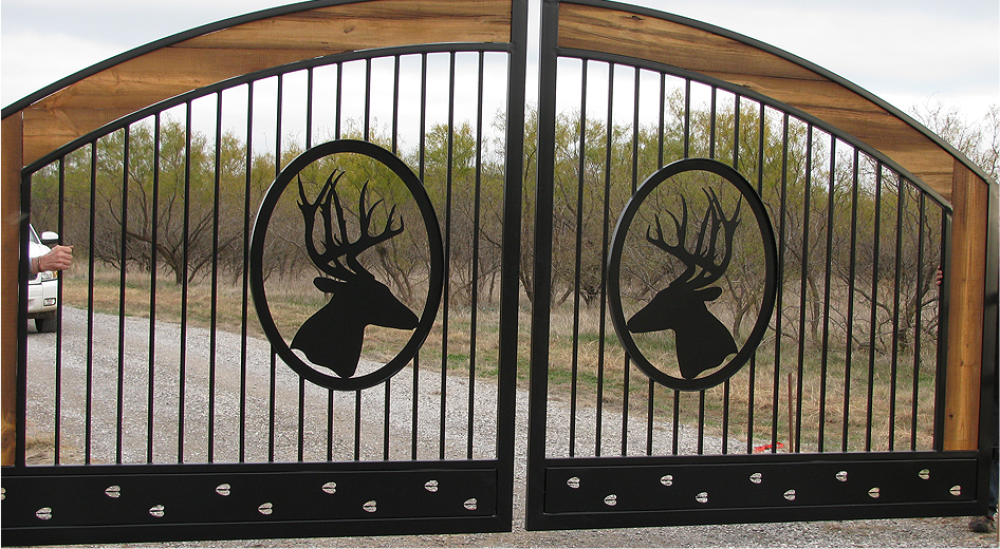 A ranch gate with ornamental deer in it.